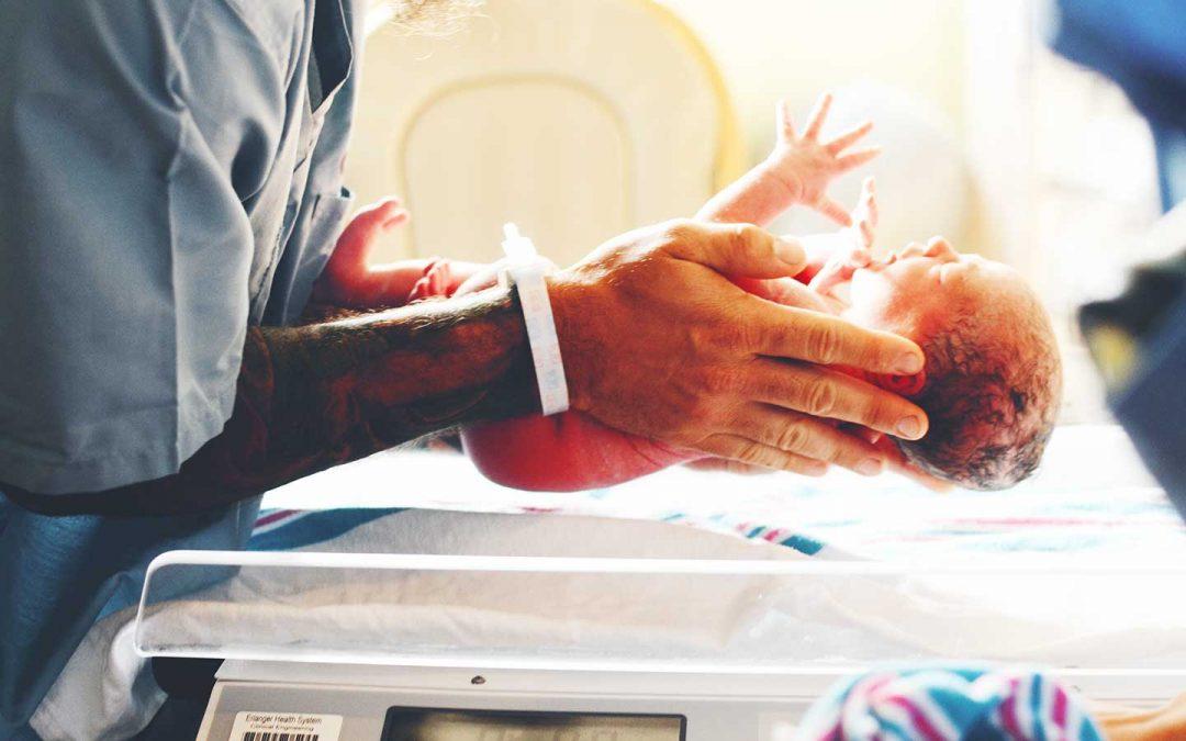 Medical professional holds newborn baby.