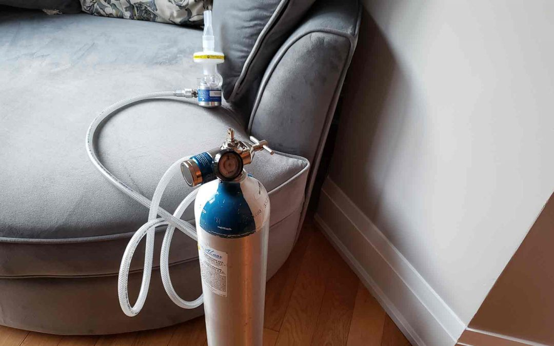 Nitrous oxide canister with tubing in front of gray chair